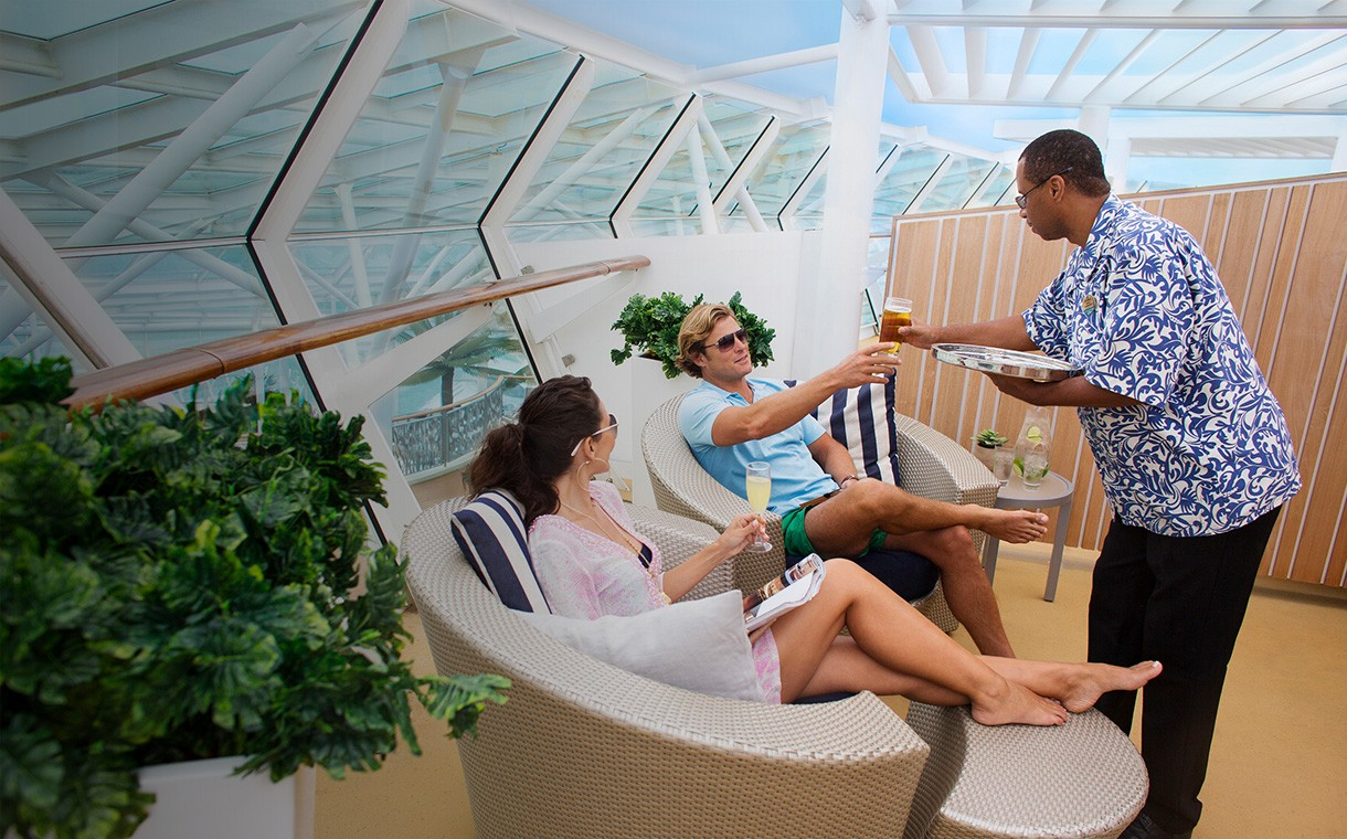 Man and woman in lounging chairs enjoying the best of Royal Caribbean cruises luxury pool service.